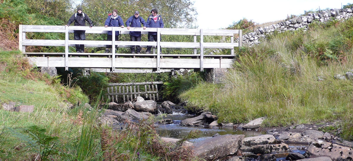 walkers on a DoE course with Mountainwise pasue on a bridge to enjoy the view a stream